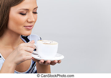 Happy beautiful woman with coffee cup in hands. pretty brunette holding cup and smelling coffee