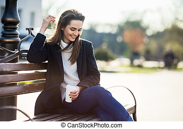 Happy beautiful woman with cup of coffee sitting on a bench in city street