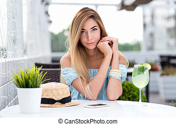 Happy beautiful woman with long hair blue gentle dress. Sits cafe table. Emotions tenderness lightness spring and summer. Tanned skin casual makeup. Waiting for lunch dinner order in a restaurant.