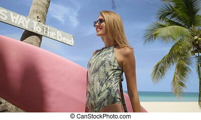 Happy beautiful woman with pink surfboard walking to the...
