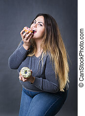 Happy beautiful young caucasian plus size model posing with donuts on a gray studio background