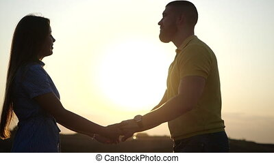 Happy beautiful young couple holding hands and lovingly looking at each other against the backdrop of sunset in the evening on the field in slow motion, close-up view. Beautiful romantic date at dawn.