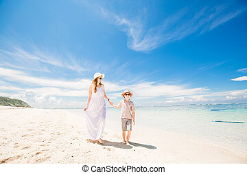 Happy beautiful young mother and son enjoying beach time with blue sky over the ocean on backgrund