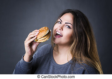 Happy beautiful young plus size model posing with hamburger...