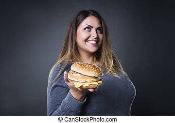 Happy beautiful young plus size model posing with hamburger on a gray studio background, xxl woman eating burger