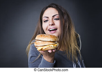 Happy beautiful young plus size model posing with hamburger ...