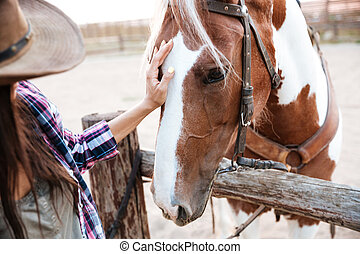 Happy beautiful young woman cowgirl taking care of her horse...