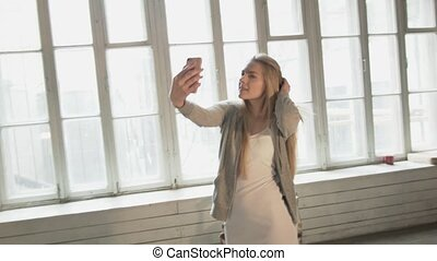 Happy beautiful young woman doing selfie on against window. Laughing blonde with a smartphone takes pictures of herself.