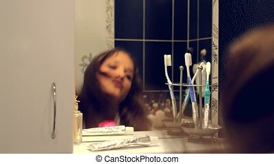 Happy beautiful young woman in a bathrobe singing and dancing in front of the bathroom mirror