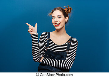 Happy beautiful young woman standing and pointing away over ...