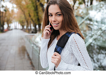 Happy beautiful young woman talking on mobile phone in park
