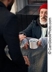 Happy beggar man sit on walking street and need help