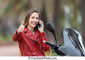 Happy biker with thumbs up on the phone