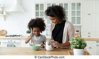 Happy biracial mom and daughter bake in kitchen together - ...