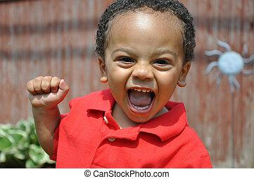 Latin Italian toddler boy smiling outside day care center