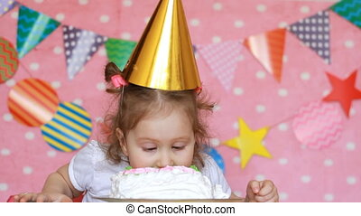 Happy birthday. A cute little girl eats a cake with dirty face and hands.