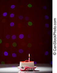 happy birthday cake shot on a red blurred background with candles