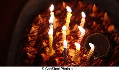 Happy Birthday cake with burning spiral candles in dark