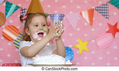 Happy birthday. Child girl eats a cake with dirty face and hands.