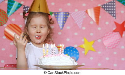 Happy birthday. Cute child girl make a wish and blows out...