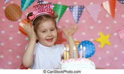 Happy birthday. Cute child make a wish and blows out candles...