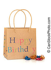 Happy birthday gift bag made of recycled paper, with coloured curly ribbons, isolated over white background.