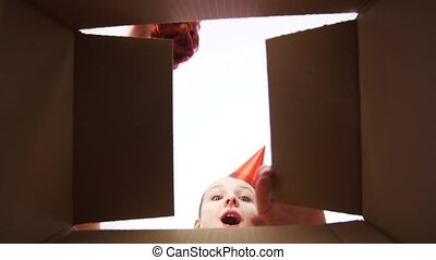 happy birthday girl in party hat opening gift box