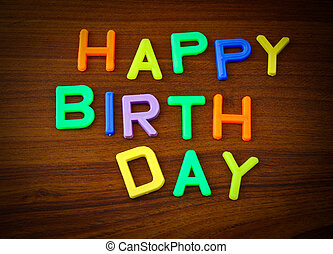 Happy Birthday in colorful toy letters on wood background