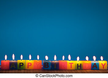 Happy birthday lit candles on blue