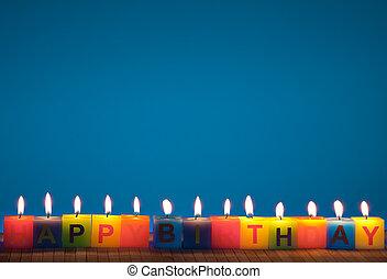 Happy birthday lit candles on blue