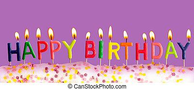 Happy birthday lit candles on purple background