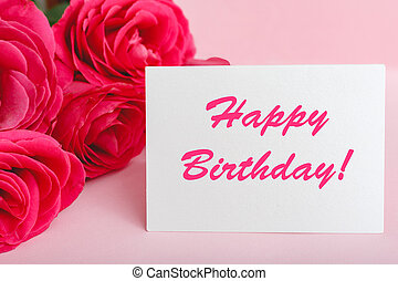 Happy birthday text on card in flower bouquet on pink background. Flower delivery, congratulation card. Greeting card in pink red roses