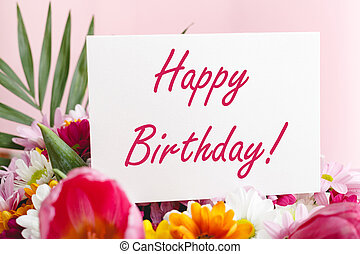 Happy birthday text on card in flower bouquet on pink background. Flower delivery, congratulation card. Greeting card in Tulips, daisies, chrysanthemum.