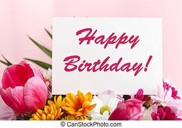 Happy birthday text on card in flower bouquet on pink background. Greeting card in Tulips, daisies, chrysanthemum beautiful spring bouquet. Flower delivery, congratulation card.