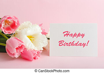 Happy Birthday text on gift card in flower bouquet. Beautiful bouquet of fresh flowers tulips with greeting card Happy Birthday on pink background.