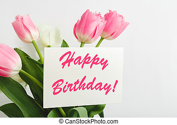 Happy Birthday text on gift card in flower bouquet. Beautiful bouquet of fresh flowers tulips with greeting card Happy Birthday on white background.