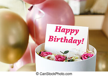 Happy Birthday text on gift card in flower box near festive pink and gold balloons. Beautiful bouquet of fresh flowers roses in box with greeting card Happy Birthday.