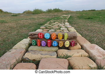 Happy Birthday text with colored stones on wood over a bricks road