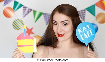 Happy birthday. The funny girl smiles, holds in hands cake and blows out a paper candle
