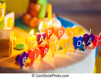 Happy birthday written in lit candles on colorful background