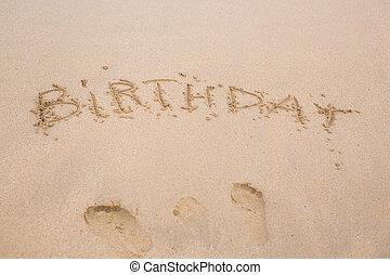 happy birthday written on the sand beach