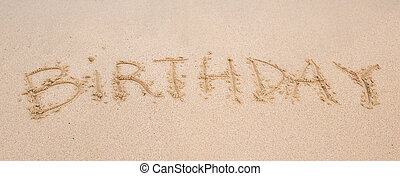 happy birthday written on the sand beach