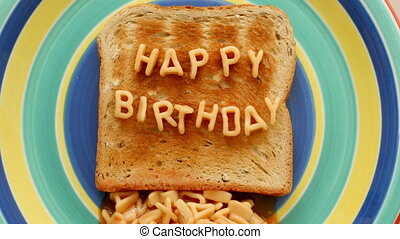 happy birthday written with alphabetti spaghetti on toast