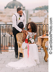 Happy black bride and groom smiling and holding hands on the terrace. Wedding day