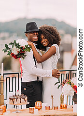 Happy black bride and stylish groom posing for camera on the terrace with cityscape on foreground