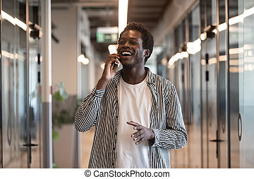 Happy black businessman talking on phone standing in office hallway
