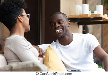 Happy black couple have fun talking relaxing in cafe