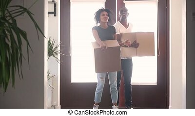 Happy black couple holding boxes talking embracing standing in hallway