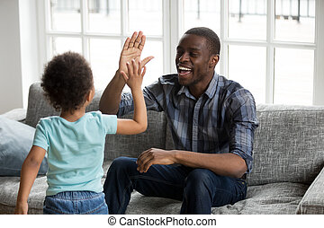 Happy black dad and son giving high-five playing at home