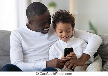 Happy black dad teaching kid son holding phone using apps